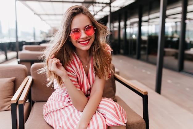 Fröhliche gutaussehende frau, die im café mit lächeln sitzt. innenporträt des aufgeregten mädchens, das auf gemütlichem stuhl kühlt.