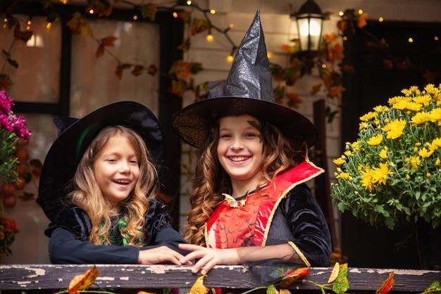 Fröhliche halloween-mädchen in hexenkostümen haben spaß im herbst in der nähe des hauses