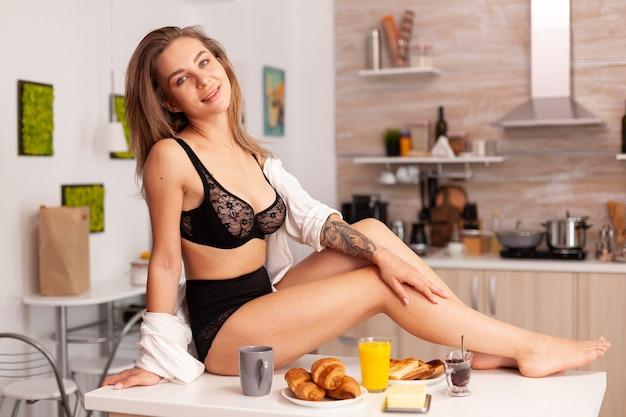 Fröhliche hausfrau in der küche zu hause, die sexy dessous trägt, die auf dem tisch sitzen. provokative junge frau mit tätowierungen in verführerischer unterwäsche.