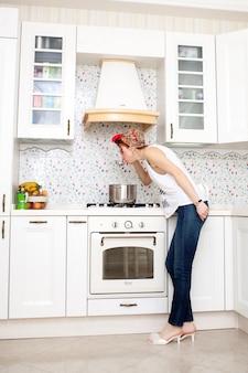 Fröhliche hausfrau in einem roten kopftuch in der küche probiert die suppe