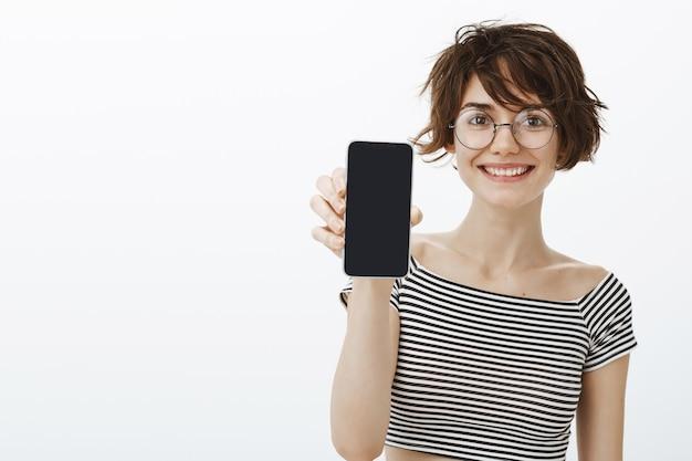 Fröhliche hipster-frau stellen anwendung vor, smartphonebildschirm zeigend
