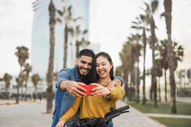 Fröhliche hispanische leute, die spaß mit dem elektrofahrrad haben, während sie selfie im freien in der stadt machen