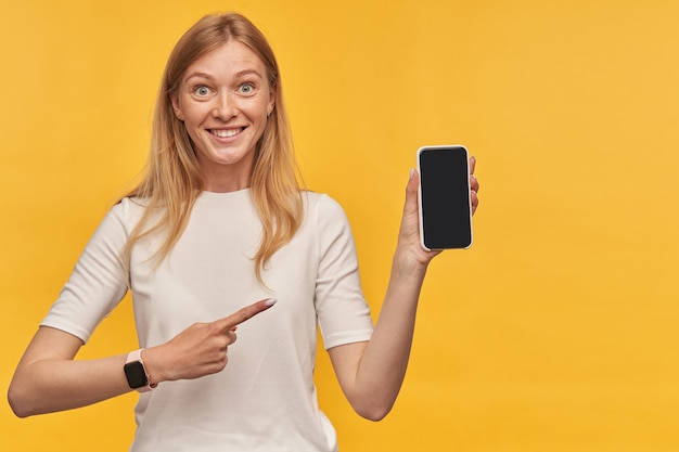 Fröhliche hübsche blonde junge frau mit sommersprossen im weißen t-shirt, die ein smartphone mit leerem bildschirm hält und auf die gelbe wand zeigt