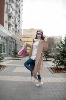 Fröhliche hübsche frau, die mit einkaufstüten steht, während sie vom einkaufszentrum zurückkommt