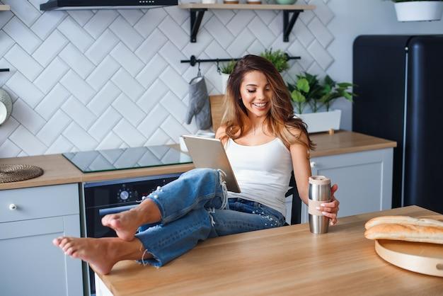 Fröhliche hübsche frau, die tablet-computer benutzt und kaffee auf der küche zu hause trinkt.