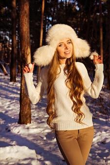 Fröhliche hübsche frau, die weißen pelzhut im winterwald hält