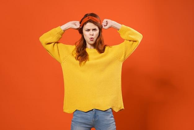 Fröhliche hübsche frau im gelben pullover moda studio dekoration retro