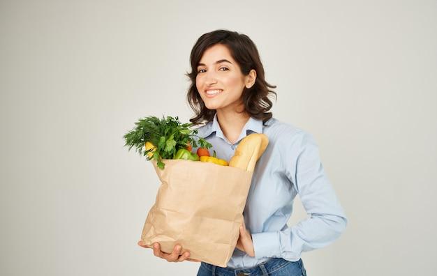 Fröhliche hübsche frau in einem hemd mit einem paket von produkten haushalt gesunde lebensmittellieferung.