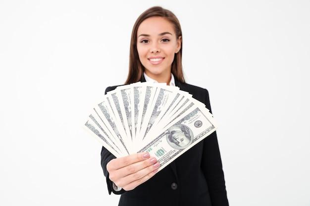 Fröhliche hübsche geschäftsfrau, die geld zeigt