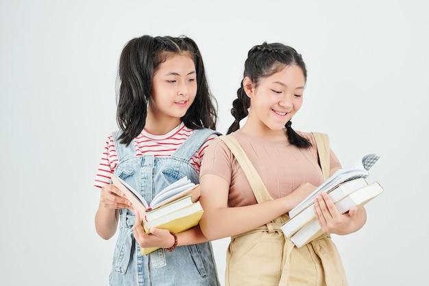 Fröhliche hübsche jugendliche schulmädchen, die schülerbücher überprüfen, die sie für klassen erhalten haben
