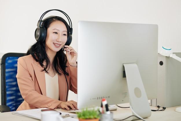 Fröhliche hübsche junge asiatische betreiberin des technischen supports im headset, die einen anruf vom kunden beantwortet