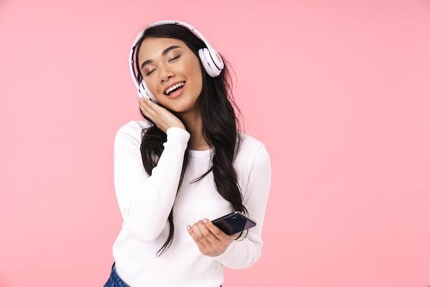 Fröhliche hübsche junge asiatische frau, die musik mit drahtlosen kopfhörern hört, isoliert, mit handy