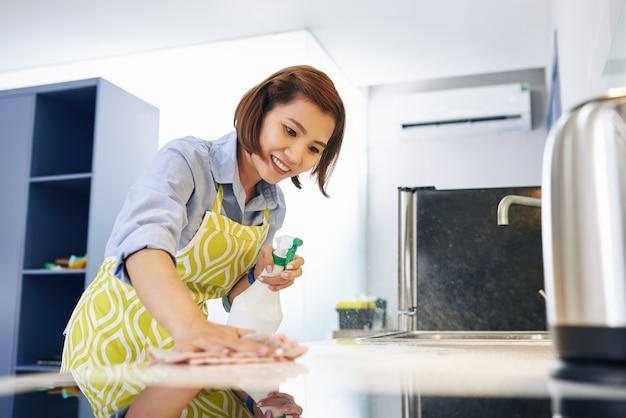 Fröhliche hübsche junge asiatische hausfrau, die küchentheke mit desinfizierendem spray reinigt