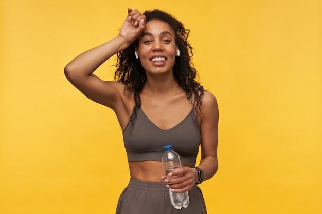 Fröhliche hübsche junge fitnessfrau hält die hand auf der stirn, hört musik mit drahtlosen kopfhörern und hält eine flasche wasser isoliert über gelber wand