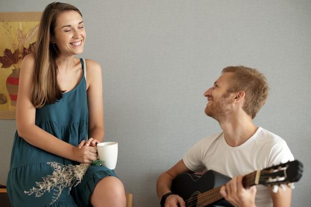 Fröhliche hübsche junge frau, die ein schönes lied ihres hübschen freundes genießt