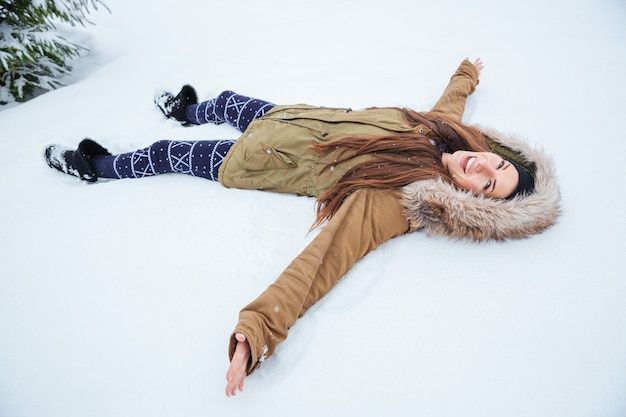 Fröhliche hübsche junge frau, die im winter draußen auf schnee liegt