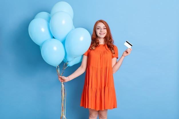 Fröhliche hübsche junge frau, die kreditbankkarte hält und mit heliumballons feiert, die über blaue wand lokalisiert werden
