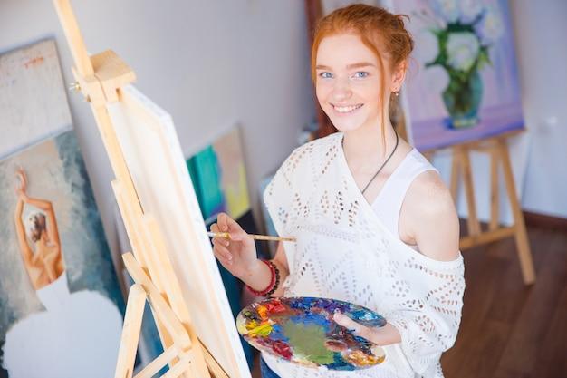 Fröhliche hübsche junge künstlerin, die in der künstlerwerkstatt steht und ein bild malt