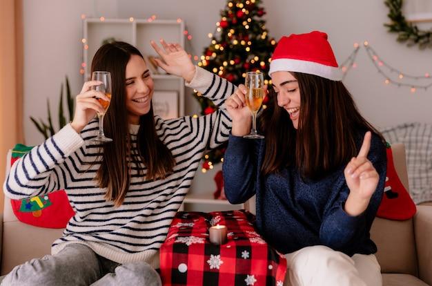 Fröhliche hübsche junge mädchen halten gläser champagner und tanzen auf sesseln sitzen und genießen die weihnachtszeit zu hause