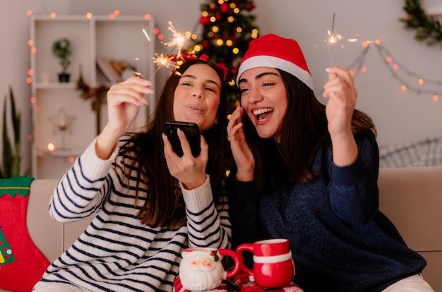 Fröhliche hübsche junge mädchen mit rentierbrille und weihnachtsmütze halten wunderkerzen und schauen auf das telefon, das auf sesseln sitzt und die weihnachtszeit zu hause genießt