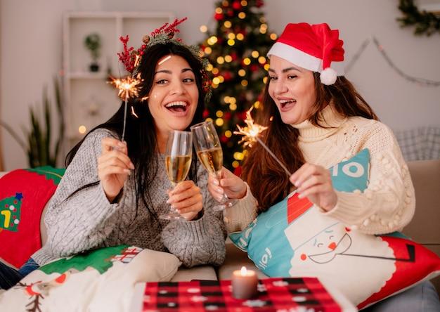 Fröhliche hübsche junge mädchen mit weihnachtsmütze halten gläser champagner und wunderkerzen, die auf sesseln sitzen und die weihnachtszeit zu hause genießen