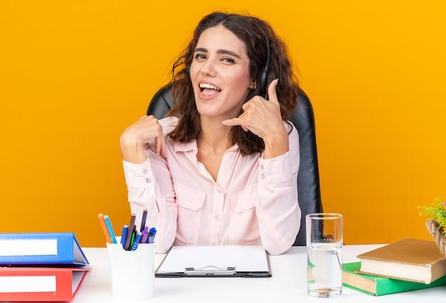 Fröhliche hübsche kaukasische callcenter-betreiberin auf kopfhörern, die am schreibtisch sitzen und mit bürowerkzeugen gestikulieren, rufen sie mich an, isoliert auf oranger wand