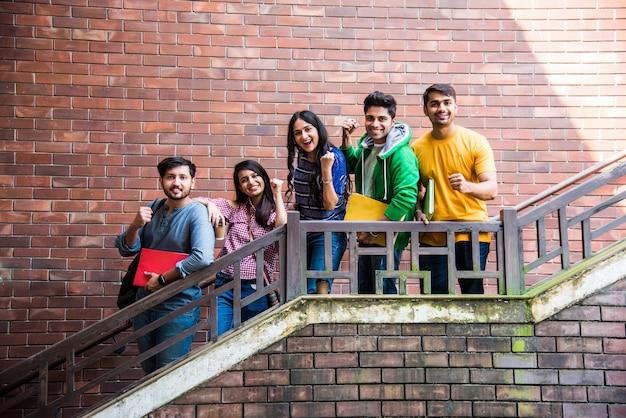 Fröhliche indische asiatische junge gruppe von college-studenten oder freunden, die im campus-korridor oder auf treppen spazieren gehen