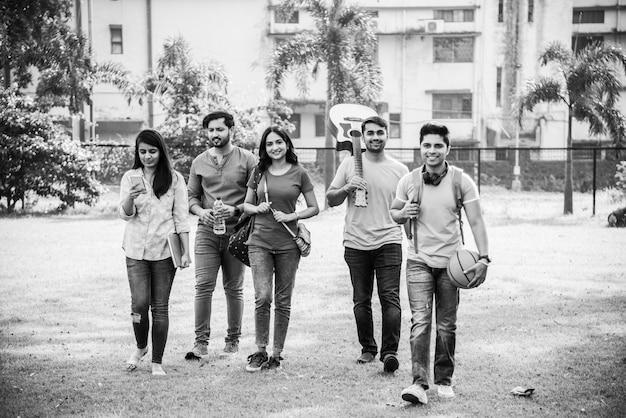 Fröhliche indische asiatische junge gruppe von college-studenten oder freunden, die zusammen lachen, während sie auf dem campus sitzen, stehen oder gehen
