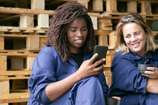 Fröhliche industriearbeiter, die zelle während der kaffeepause benutzen