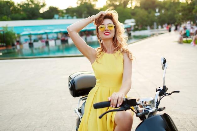 Fröhliche ingwerfrau in der gelben brille und im weinlesekleid, die auf stilvollem motorrad sitzen. urlaubsstimmung. sonniger sommertag. rote lippen.