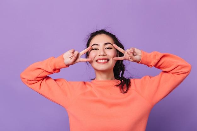 Fröhliche japanische frau, die friedenszeichen zeigt. lachende asiatische weibliche modell gestikuliert auf lila hintergrund.
