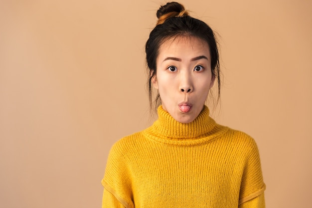 Fröhliche japanische frau mit pullover, die ihre zunge herausstreckt und auf die vorderseite schaut, isoliert über beige wand im studio?