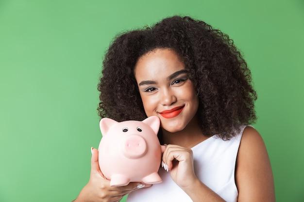 Fröhliche junge afrikanische frau, die kleid trägt, das lokal steht und sparschwein zeigt