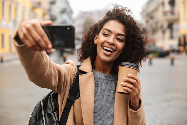 Fröhliche junge afrikanische frau, die mantel trägt, der draußen geht, kaffeetasse zum mitnehmen hält und ein selfie nimmt