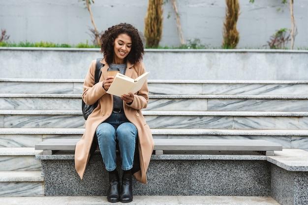 Fröhliche junge afrikanische frau, die mantel trägt, der draußen sitzt, kaffeetasse zum mitnehmen hält, ein buch liest
