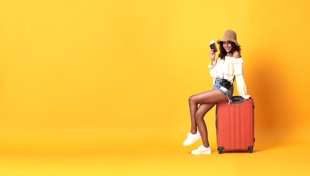 Fröhliche junge afrikanische frau gekleidet in sommerkleidung sitzend auf einem koffer auf kopie raum gelbe wand.