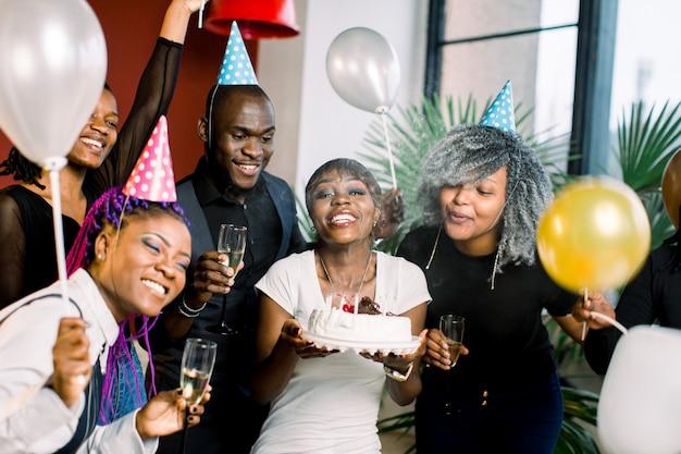 Fröhliche junge afrikanische gesellschaft feiert geburtstag und hat einen kuchen mit kerzen
