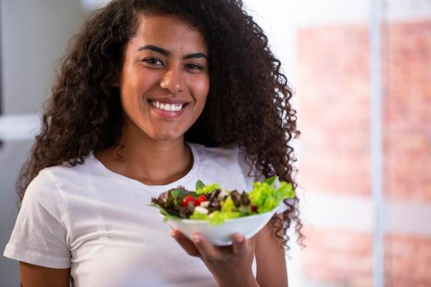 Fröhliche junge afroamerikanische frau, die gemüsesalat in der hauptküche isst