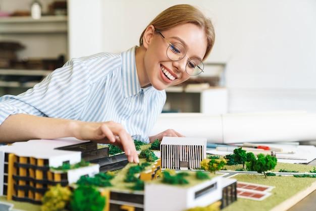Fröhliche junge architektin in brillen, die entwurf mit hausmodell entwirft und am arbeitsplatz sitzt