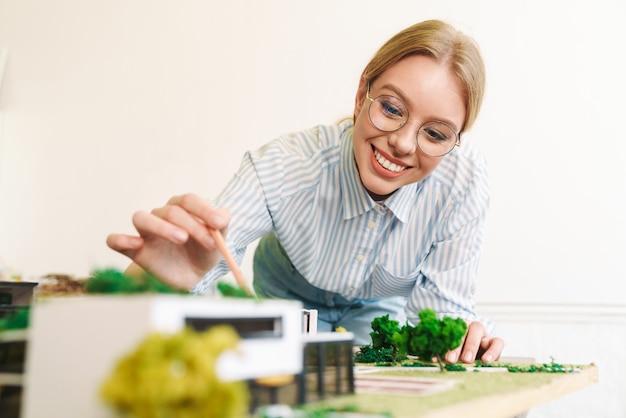 Fröhliche junge architektin in brillenentwurf mit hausmodell am arbeitsplatz