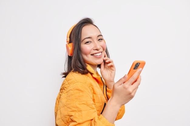 Fröhliche junge asiatin steht seitlich gegen weiße wand hält smartphone hört musik über drahtlose kopfhörer trägt orangefarbenen anorak genießt lieblingslied verwendet spezielle app auf dem handy mobile