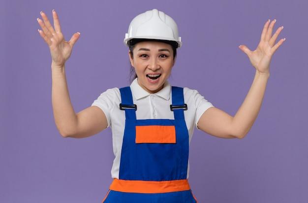 Fröhliche junge asiatische baumeisterin mit weißem schutzhelm stehend mit erhobenen händen