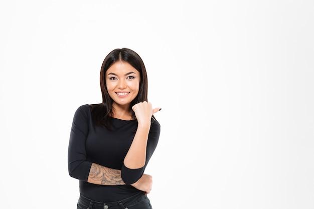 Fröhliche junge asiatische dame, die isoliert steht und auf copyspace zeigt.