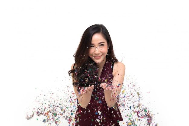 Fröhliche junge asiatische frau, die mit dem bunten konfetti lokalisiertes thailändisches modell feiert