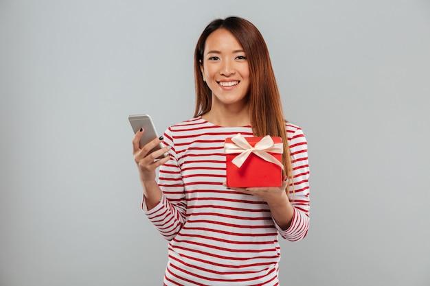 Fröhliche junge asiatische frau, die per telefon hält, das geschenk hält.