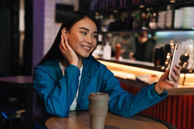 Fröhliche junge asiatische frau, die selfie auf dem handy macht und lächelt, während sie im café sitzt