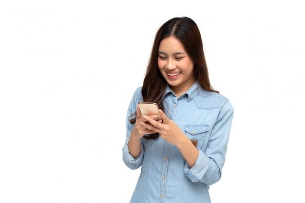 Fröhliche junge asiatische frau, die smartphone verwendet und gute nachrichten von der nachricht auf der mobilen chat-anwendung erhält