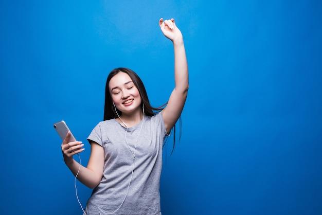 Fröhliche junge asiatische frau in den kopfhörern, die musik hören und lokalisiert über blaue wand tanzen