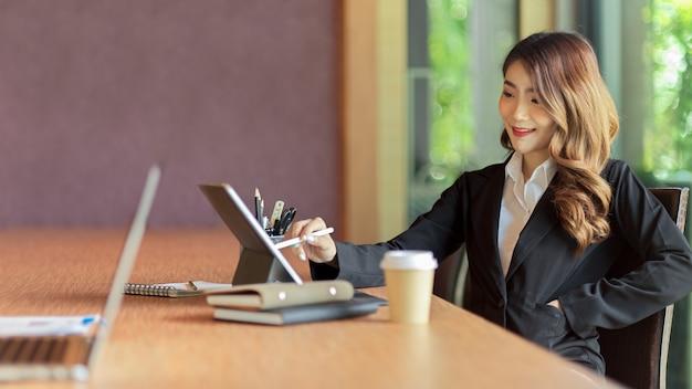 Fröhliche junge asiatische geschäftsfrau, die an tablet-zeichnungsgeschäftsmodell arbeitet