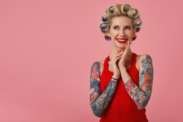 Fröhliche junge attraktive blonde dame mit tätowierten händen, die lächelnd und träumerisch nach oben schauen, bevorstehende party vorhersagen und sich darauf vorbereiten, vor rosa hintergrund stehend